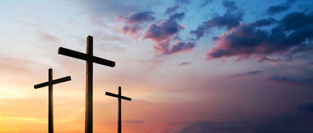 Easter concept. Cross of Jesus Christ empty over dramatic sunrise sky panorama with sclouds.