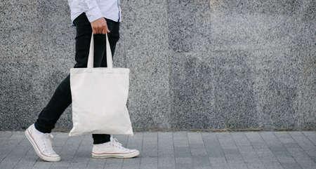 White textile eco tote bag against urban city background. White shopping bag mock up.