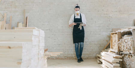 Confident woman working as carpenter in her own woodshop. She using a tablet pc and writes notes while being in her workspace. Small business concept.