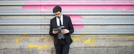 Businessman using a tablet pc outside on the city street wearing elegant clothes 版權商用圖片