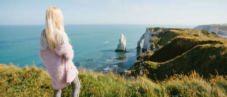 Tourist girl looking from above to the bay and alabaster cliff bay of Etretat, France Reklamní fotografie