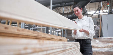 Business woman worker in the carpentry factory using tablet pc. Carpentry factory. Factory for the production of parquet board 版權商用圖片