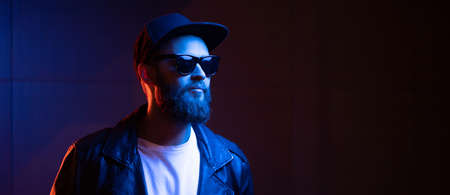 Hipster handsome man on the city streets being illuminated by neon signs. He is wearing leather biker jacket or asymmetric zip jacket with black cap, jeans and sunglasses. 版權商用圖片