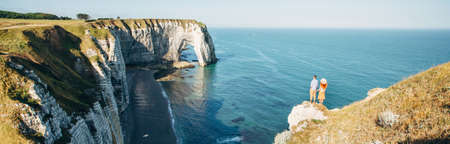Couple looking at Etretat cliffs along the ocean shore in France