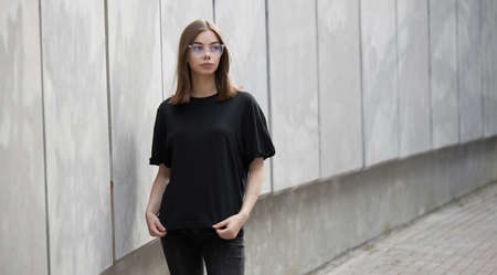Woman or girl wearing black blank cotton t-shirt with space for your logo, mock up or design in casual urban style 版權商用圖片