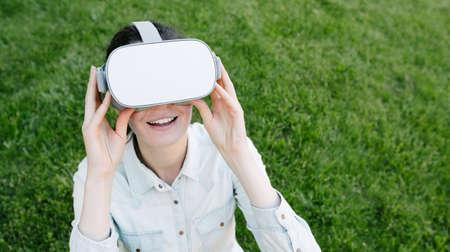 Woman using virtual reality glasses outside on a green grass 版權商用圖片