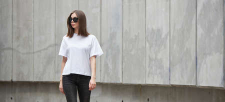 Girl or woman wearing white blank t-shirt with space for your logo, mock up or design in casual urban style 版權商用圖片