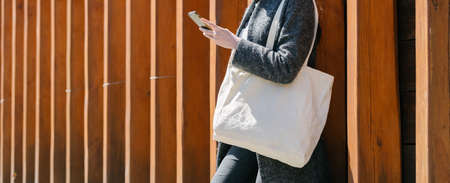 Woman holding white textile tote eco bag in urban area. Ecology or environment protection concept. White eco bag for mock up.