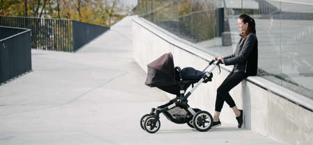 Mother with a pram or stroller on modern city streets walking and relaxing in autumn 版權商用圖片