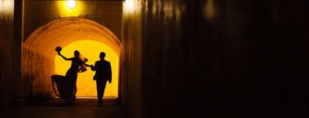 Bride and groom walking away jumping in a dark tunnel 版權商用圖片