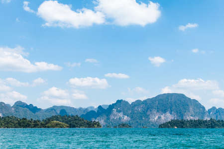 thani: Blue clear water and blue sky with rock mountains reservoir lake at Ratchaprapa Dam Surat Thani, Thailand Stock Photo