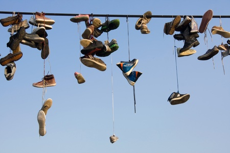 Old various shoes hanging on wire photo