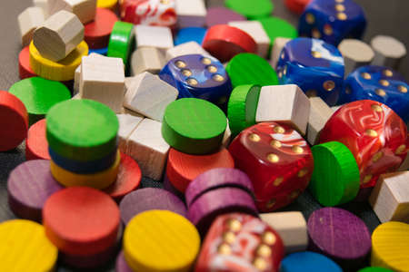 a multicolored pile consisting of dice and wooden chips close-up