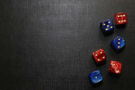 multi-colored dice lying on a black textured surface