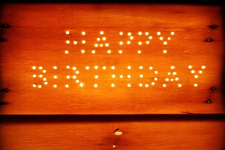 Happy birthday on a rustic wooden board, isolated on black background photo