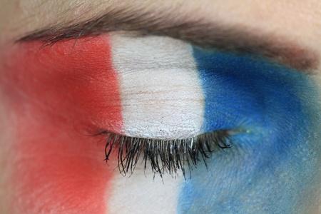 彼女の目に描かれたフランス語フラグを持つ少女