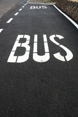 Bus stop sign painted on asphalt road