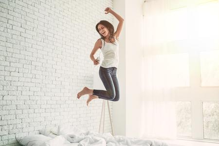 이어폰에 행복 한 젊은 여자는 스마트 전화로 음악을 듣고, 침대에 점프, 노래 하 고 웃 고