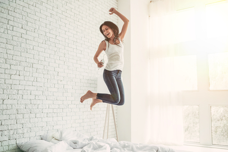 Happy young woman in earphones is listening to music with smart phone, jumping on bed, singing and smiling Stockfoto