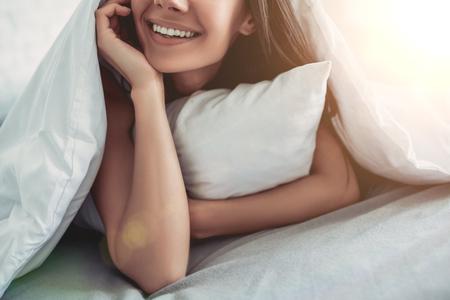 Bebouwd beeld van mooie glimlachende jonge vrouw omvat door deken terwijl het liggen op bed