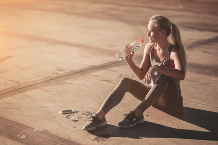 Attractive sporty girl is having rest and drinking water after the jogging on street. Smart phone with headphones are nearby. Stock Photo