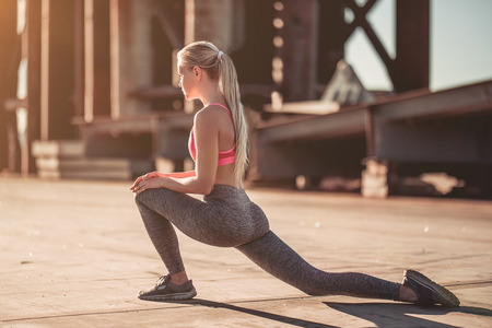 Attractive sporty girl is stretching on street during the sunset Stock Photo
