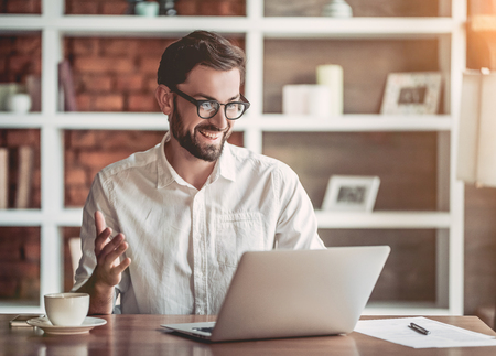 Handsome businessman in eyeglasses is working with laptop in cafe and smiling.