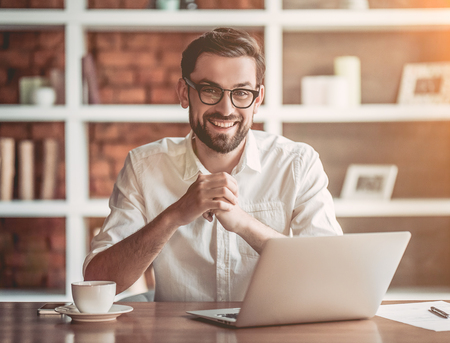 Handsome businessman in eyeglasses is working with laptop in cafe, smiling and looking at the camera. Lizenzfreie Bilder