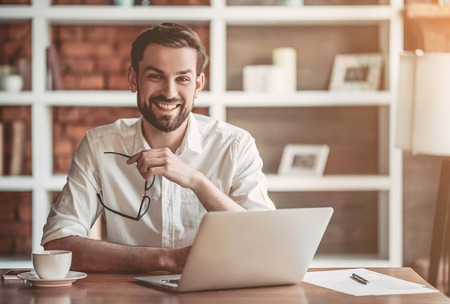 Handsome businessman with eyeglasses in hand is working with laptop in cafe, smiling and looking at the camera.