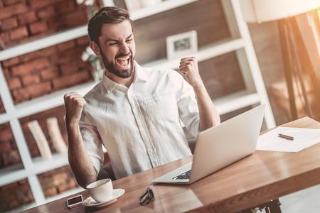 Feliz apuesto hombre de negocios está trabajando con la computadora portátil en el café. Buenas noticias. ¡Sensación de victoria!