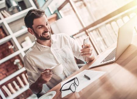 잘 생긴 남자 카페에서 커피 한 잔 마시는 미소하고 스마트 전화 찾고.