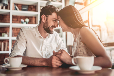 Couple in love is sitting in cafe face to face, holding hands and smiling Stock Photo