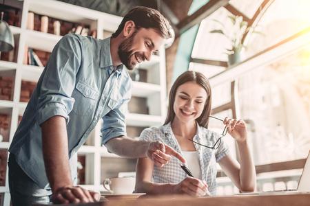 若いカップルは、カフェで働いています。最新のニュースを議論して、笑みを浮かべてします。