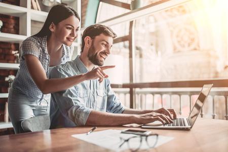 Jong koppel werkt in cafe op laptop en glimlachen. Stockfoto
