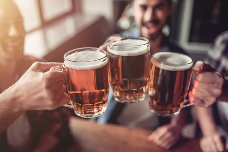 Cheers, my friends! Cropped image of three handsome men are drinking beer, celebrating meeting and smiling. Stock Photo
