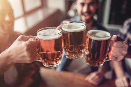 Saluti, amici miei! L'immagine ritagliata di tre bei uomini sta bevendo birra, celebra l'incontro e sorride. Archivio Fotografico - 80921372