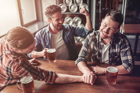 Drie knappe mannelijke vrienden drinken bier in bar en hebben plezier in armwrestling.