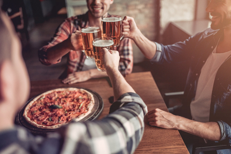 Cheers! Side view of three male friends in bar drinking beer and eating pizza. Banco de Imagens