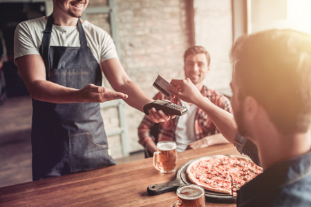 술집에서 신용 카드를 통해 지불하는 남자.