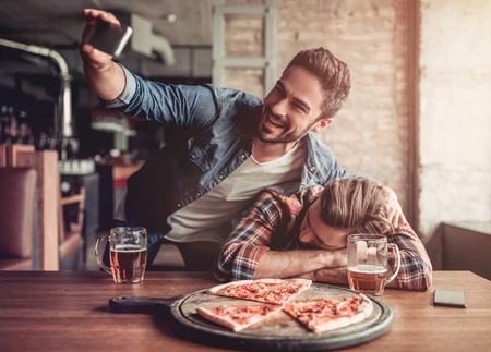 exhausting: Happy smiling men is making selfie with his drunk friend on a smartphone. Stock Photo