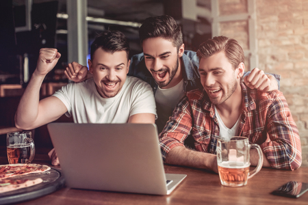 Happy excited fans are looking into the laptop, drinking beer and smiling. Stock Photo