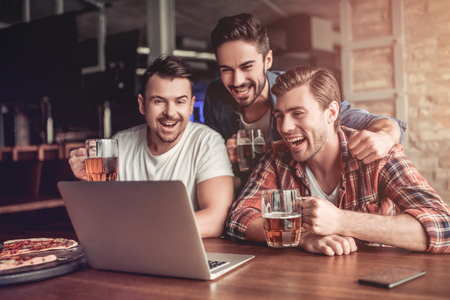 Happy excited fans are looking into the laptop, drinking beer and smiling. Stockfoto