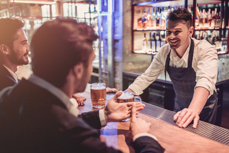 Handsome businessmen in bar are drinking beer and communicating with cheerful bartender. 版權商用圖片