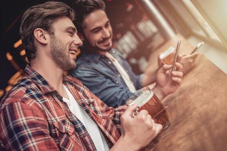 ハンサムな男性の友人 2 人の手でスマート フォンでビールを飲むと、笑みを浮かべてバー。