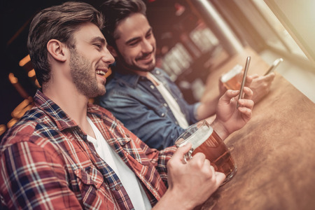 Due amiche amici maschi nel bar birra birra con smartphone in mano e sorridente. Archivio Fotografico - 80942795
