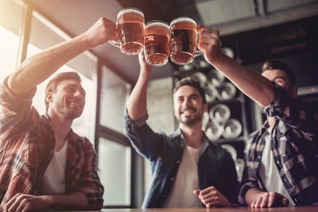 Cheers, my friends! Three handsome men are drinking beer, celebrating meeting and smiling. Stockfoto