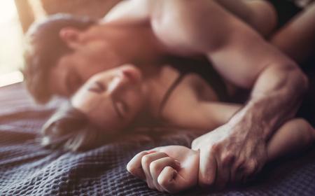 아름 다운 열정적 인 부부는 침대에서 섹스를하고있다. 남자는 꼭대기에있다. 스톡 콘텐츠