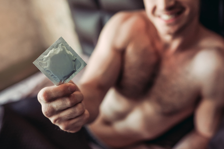 condones: Cropped image of a smiling man holding condom in hand while lying on bed. Foto de archivo
