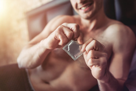 Cropped image of a smiling man holding condom in hand while lying on bed. Stock Photo