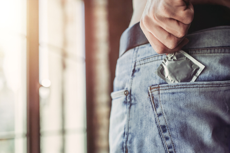 Cropped image of a man holding condom in hand while taking it from jeans. Фото со стока
